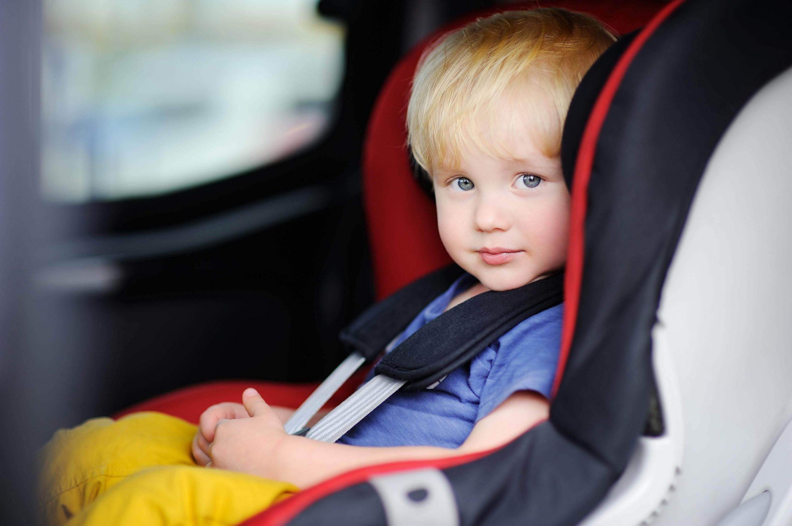ילד יושב בכסא בטיחות