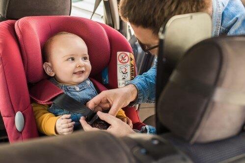אבא חוגר את התינוק שלו במושב בטיחות