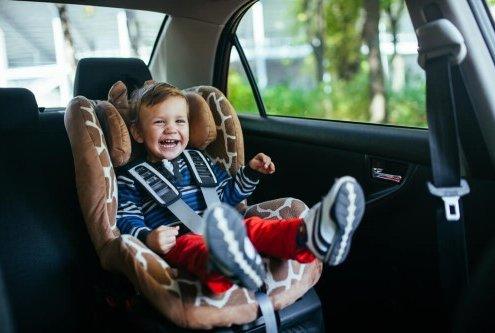 ילד מחייך בכיסא בטיחות ברכב