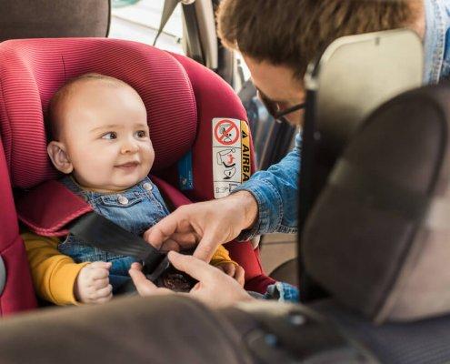 תינוק יושב במושב בטיחות עם התקן איוזפיקס