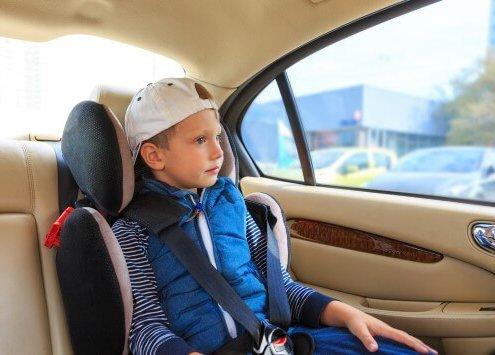 ילד יושב בבוסטר עם רתמות